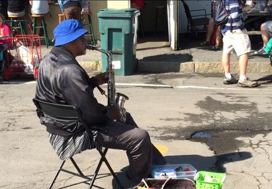 Hosea Taylor Jr. playing at the Rochester Public Market. He used some of the funds collected from passersby to pay for instruments for local children.