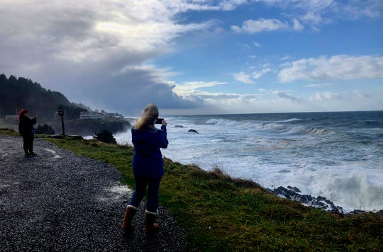 In this Jan. 11, 2020 photo onlookers use smartphones to film waves crashing ashore at Rodea Point in Lincoln County, Oregon during an extreme high tide that coincided with a big winter storm.