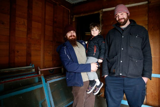 Nick Haas, of Portland, left, with his son, Zelyn Haas, 4, and Chance Wiesner, of Hayesville, look inside the home built in 1864.