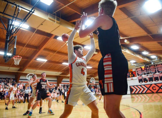 Eli Boomgarden of Viborg-Hurley passes the ball to teammate Grant Mikkelsen through the reaching arms of Tyce Ortman of Canistota on Tuesday evening, Feb. 4, at Canistota High School.