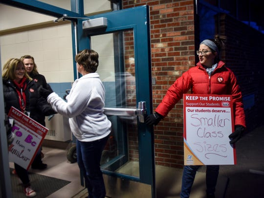 Second grade teacher Kayla Nettestad holds the door for her fellow teachers before a walk-in protest on Wednesday, Feb. 5, 2020 at Robert Frost Elementary School. Several schools around the district were protesting a lack of funding for education by the state.