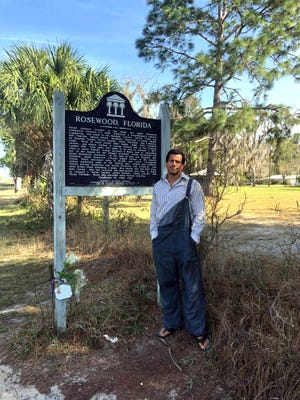 Eric Olson stands next to the historical marker that stands where Rosewood once flourished.
