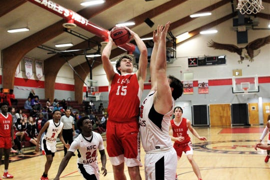 Leon junior forward DJ Campbell goes up for a basket in the paint over NFC center JT Price as Leon's boys basketball team beat NFC 68-44 on Feb. 4, 2020.