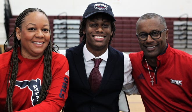 Florida High quarterback Willie Taggart Jr. celebrates signing with Florida Atlantic alongside mother Taneshia and father Willie Taggart Sr., who is FAU's new head coach.