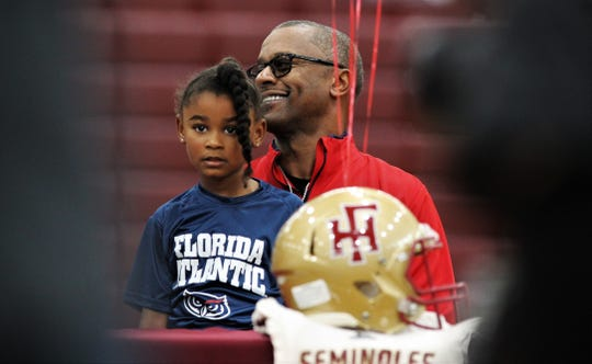 New Florida Atlantic coach Willie Taggart Sr. holds daughter Morgan while waiting for son Willie Taggart Jr.'s signing ceremony to being on national signing day, Wednesday, Feb. 5, 2020.
