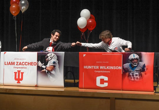 Jensen Beach High School football players Liam Zaccheo (left) and Hunter Wilkinson celebrate together at the start of their National Signing Day ceremony held inside the school's auditorium on Wednesday Feb. 5, 2020, in Jensen Beach. Zaccheo signed with Indiana University, Wilkinson with Central College in Iowa.