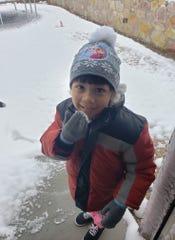 Anaya Caro, 6, prepares to take a taste of snow in El Paso.