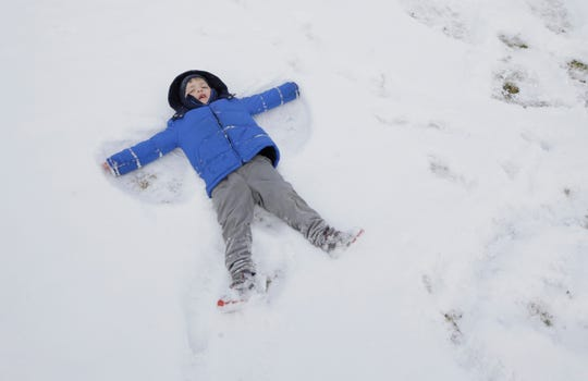 Mikey Hagerty makes a snow angel at Officer Andrew Barcena Park Wednesday in northeast El Paso.