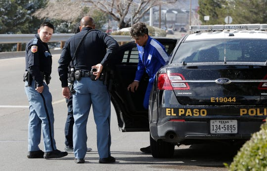 A man exits an El Paso police car Wednesday at Cielo Vista Mall after reports of robbery suspects were stopped by police.