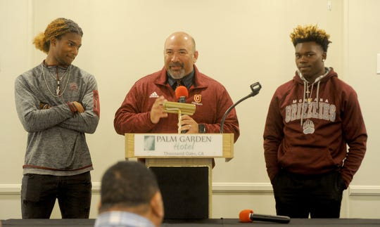Oxnard High head coach Jaime Moreno, middle, talks about Aaron Fontes, left, and Xavier Harris — who are both headed to the University of Montana — during the Ventura County Football Coaches Association's annual signing luncheon at Palm Garden Hotel in Newbury Park on Wednesday.