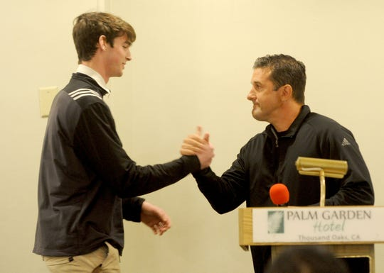 St. Bonaventure High's Gavin Beerup, left, shakes hands with his former head coach Tony Henney during the Ventura County Football Coaches Association's annual signing luncheon at Palm Garden Hotel in Newbury Park on Wednesday. Beerup will play at the University of Wyoming in the fall.