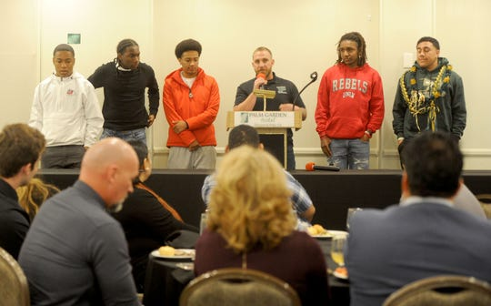 Pacifica High head coach Mike Moon, center, talks about his players — Malik Sherrod (left to right), Kyrie Wilson, Swanson Nunnery, Nohl Williams and Pup Aina — at the Ventura County Football Coaches Association's annual signing luncheon at Palm Garden Hotel in Newbury Park on Wednesday. Sherrod will play at Fresno State; Wilson is headed to Cal Poly San Luis Obispo; Nunnery is going to Western Colorado; Williams will play at UNLV; and Aina is headed to Sacramento State.