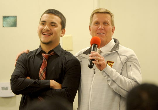 Simi Valley High head coach Jim Benkert, right, gets a smile out of Elijah Leiva, left, during the the Ventura County Football Coaches Association's annual signing luncheon at Palm Garden Hotel in Newbury Park on Wednesday. Leiva has signed to play for Western Colorado.