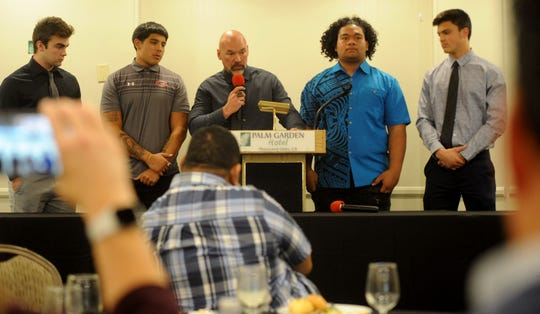 Grace Brethren head coach Josh Henderson, middle, is surrounded by his players (left to right) — son Josh Henderson, Danny Valenzuela, Soane Toia and Nate Bennett — at the Ventura County Football Coaches Association's annual signing luncheon at Palm Garden Hotel in Newbury Park on Wednesday. Josh Henderson is headed to Cal Poly San Luis Obispo; Valenzuela is going to Western Colorado; Toia will play for San Jose State; and Bennett will play for Portland State.