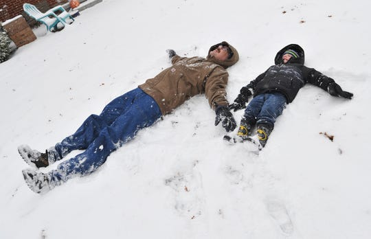 Peter Farr and his son Caleb made snow angels, Wednesday morning.