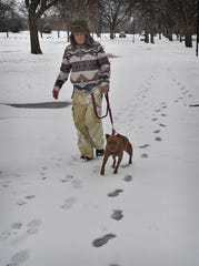 Donnie Robertson and his dog, Sheba, go for a walk in the snow at Lucy Park Wednesday morning.