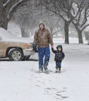 Peter Farr, left, and his son, Caleb,4, walks home from the park, Wednesday morning. Peter said this is the first time Caleb has ever seen a real blanket of snow.