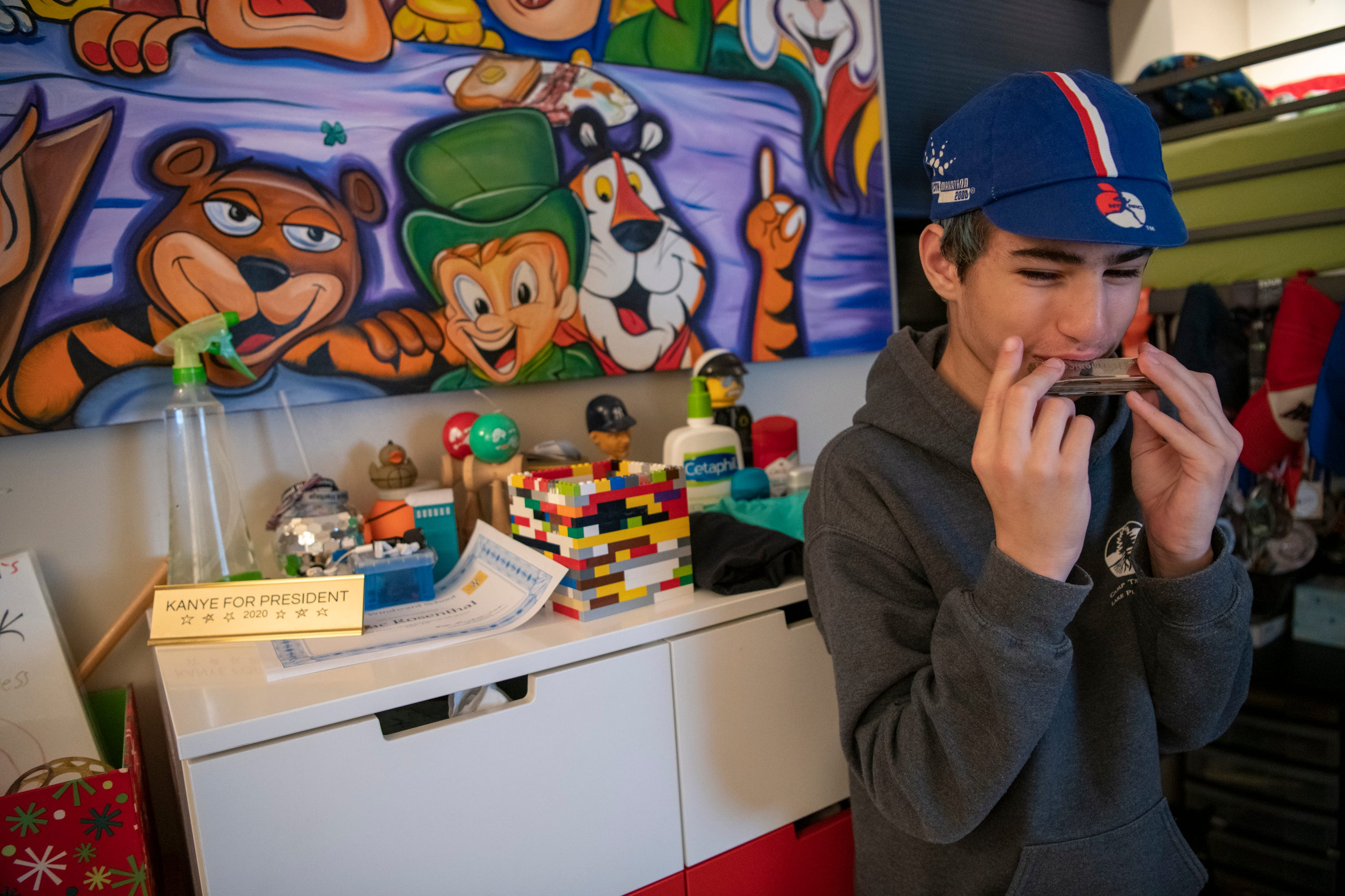 Isaac Rosenthal plays harmonica in his bedroom.
