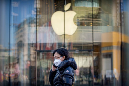 A woman wears a face mask as she walks past an Apple store that is temporarily closed due to health concerns in Beijing, Tuesday, Feb. 4, 2020.