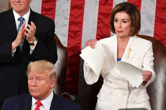 Vice President Mike Pence claps as House Speaker Nancy Pelosi appears to rip up a copy of President Donald Trumps's speech after the State of the Union address at the US Capitol in Washington, DC, on Feb. 4, 2020.