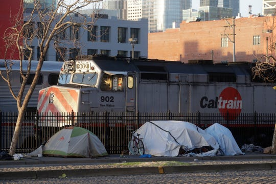 Tents are shown in front of a Caltrain commuter rail in San Francisco. The city has a surging homelessness problem that has drawn the ire of President Donald Trump. A homeless man suspected of burglary recently attacked police officers; the local DA's decision to hold off on prosecuting the man drew fire from pro-police groups warning that the new DA, Chesa Boudin, was soft on crime.