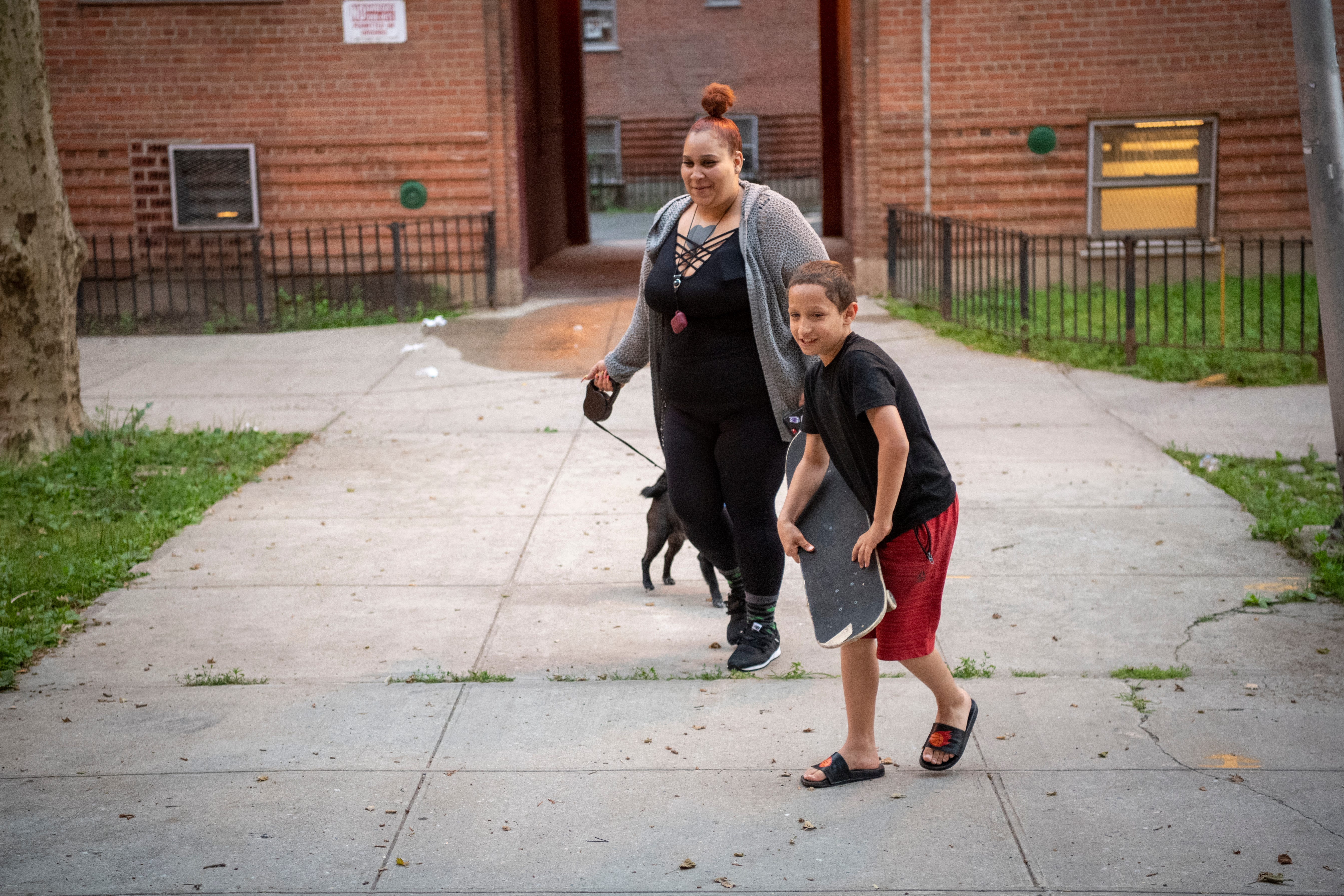 Landon Rodriguez plays with his skateboard while his mother, Yolanda, walks their dog, Buddy.