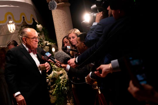 US President Donald Trump's personal lawyer Rudy Giuliani speaks to the press outside the grand ballroom as he arrives for a New Year's celebration at Mar-a-Lago in Palm Beach, Florida, on December 31, 2019.