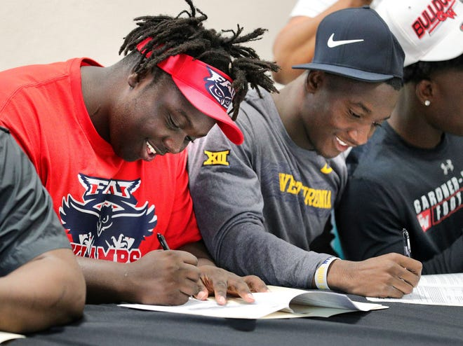 Evan Anderson, left, and Avarius Sparrow, sign their commitment papers during a national signing day ceremony at Jones High School, Wednesday, Feb. 5, 2020, in Orlando.