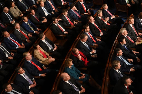Members of Congress listen as President Donald J. Trump delivers the State of the Union address from the House chamber of the United States Capitol in Washington.