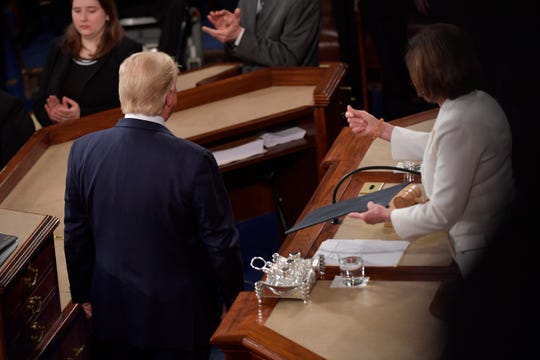 US President Donald Trump passes the written address to Speaker of the House Nancy Pelosi, but does not shake her hand before President Donald J. Trump delivers the State of the Union address from the House chamber of the United States Capitol in Washington.