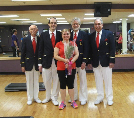 A quartet from the Red Bank Area Chapter of the Barbershop Harmony Society poses with a recipient of a singing valentine at a local gym.