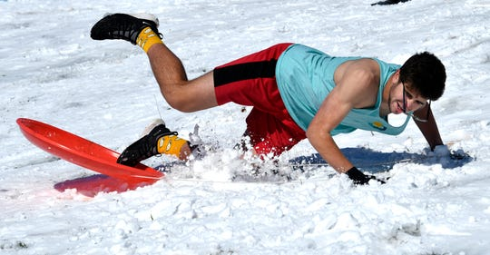 Andrew Clute,a junior at Abilene High School, falls into the snow after trying to ride a sledding disc standing up at Wildcat Disc Golf Course Thursday. A small group of students and parents were taking advantage of the city's second snow day before it melts.