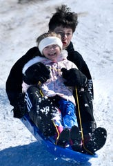 Caden, 11, and Hadley, 6, Camp react as they land coming off a snow jump at Wildcat Disc Golf Course on Thursday. The pair kept at it several more times as their father Brent watched.