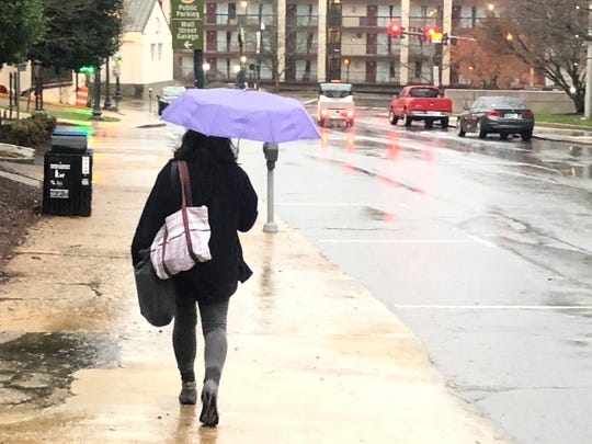 Flood watches and warnings are in store for Western North Carolina on Feb. 2, 2020, as 4-6 more inches of rain are expected. Here a woman makes her way down Otis Street in downtown Asheville.