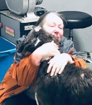 Brenda Black, of Montrose, embraces her 1-year-old dog named Odin for the first time in nine months after he ran from her home and was found in Candor.
