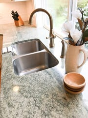 The homeowner in a kitchen remodel envisioned splashes of color in her cabinetry but went a different route after falling in love with granite with splashes of green, grey and white.