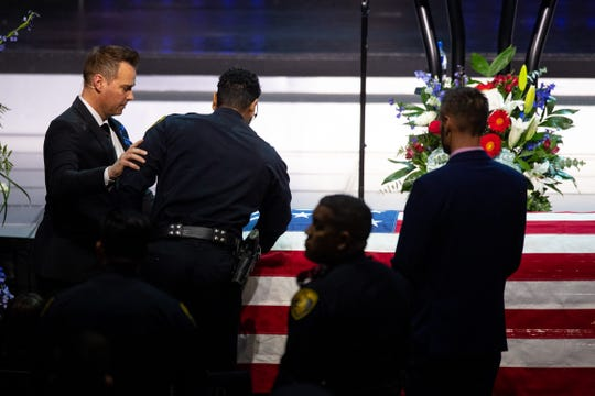 Corpus Christi Police Officer Michael Love stands over the casket of Officer Alan McCollum who was killed in the line of duty. Love was injured in crash that killed McCollum on Friday, Jan. 31, 2020.
