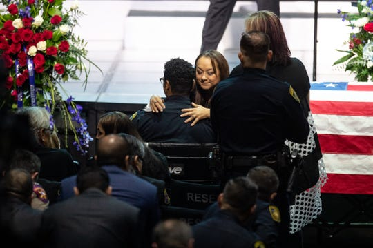 Michelle McCollum hugs Officer Michael Love during the funera Thursday for her husband, Officer Alan McCollum. Love was injured in crash that killed McCollum on Friday, Jan. 31, 2020.