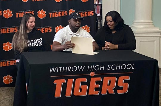 Daniel Ingram, quarterback at Withrow High School, signed his letter of intent to play for the University of Cincinnati with his godmother to the left and his mother, Andrea Jackson, on the left.
