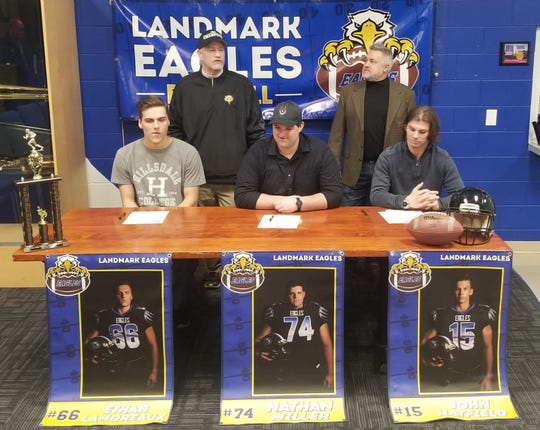 Landmark Christian football players who signed their letters of intent were, from left, Ethan Lamoreaux, Hillsdale College; Nathan Miller, University of the Cumberlands; and John Hatfield, Kentucky Christian University. Behind them are coaches Mike Goodpaster and Mike Grabel.