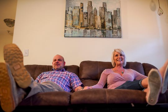 Bret Fenske, left, and Susan Fenske, who will celebrate their 30th anniversary in October, sit on the couch in their favorite relaxing position where they normally watch movies at their apartment in Clarksville, Tenn., on Tuesday, Feb. 4, 2020.