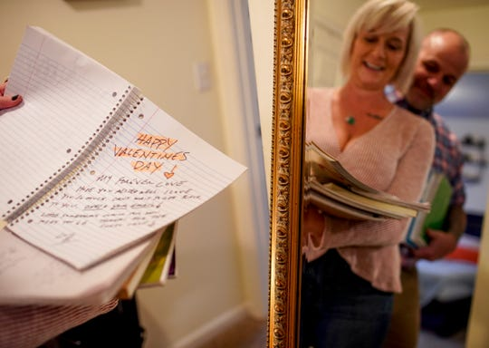 Susan Fenske turns to a page with a Valentine's Day note from a past year while sifting through notebooks she and her husband, Bret, have filled with love notes at their apartment in Clarksville, Tenn., on Tuesday, Feb. 4, 2020.