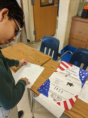 Shourya Chhabra of Roselle Park puts the finishing touches on his amendment poster.