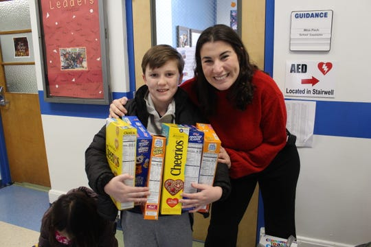 Alyssa Pech and Brendan Archbold smile for the camera as they collect cereal boxes to be donated to a local food pantry.