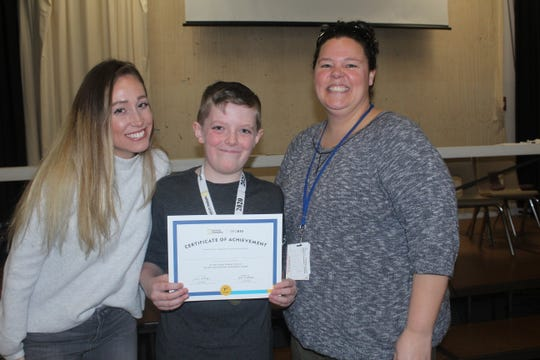 Tiffany Serafin (left) and Nicole Panos (right) stand proudly with Aidan Segerson after he won the Woodland School GeoBee!