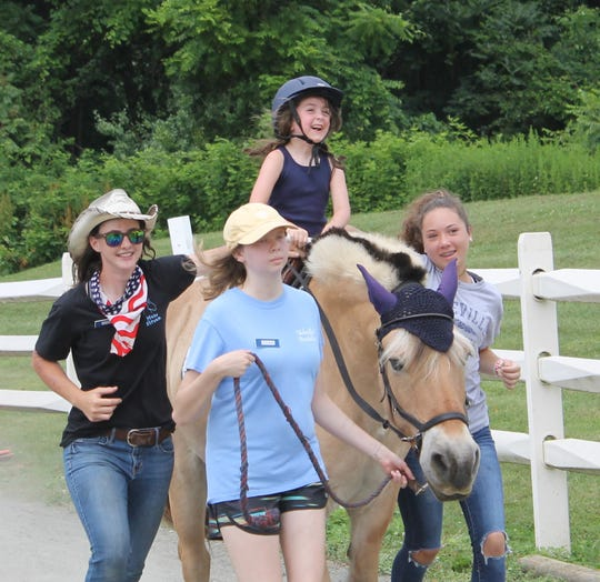 Tess Evans of Glen Gardner loves Minnie's fast trot during summer camp in 2019. Assisting Tess are (left to right) Sarah Perry of Glen Rock, Colleen Melilli of the Basking Ridge section of Bernards, and Ava Smadi of Califon.