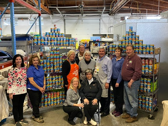 Rotarians at the food bank with the cans of soup. Pictured are Laura DePrado, Cathy Callahan, Roseann Brown, Doug Bateman (rear), Marie Scannell, Kip Bateman, Maria Donegan, and John Shockley.
