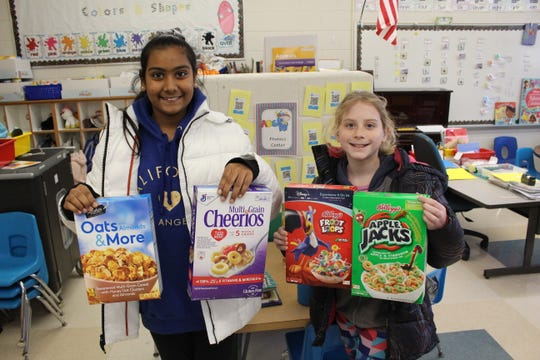 Jahnavi Ponnolu and Sydney Paradise walk from classroom to classroom throughout Central School to collect donated boxes of cereal.
