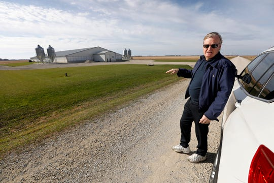 """In this Oct. 29, 2018, photo, Brad Trom looks over a concentrated animal feeding operation, or CAFO, near his farm in Blooming Prairie, Minn. Critics say yesteryear's barnyard whiffs were nothing like the overpowering stench from today's supersized operations. """"You don't want to be anywhere near them,"""" said Trom, a fourth-generation crop farmer, who lives within three miles of 11 structures housing 30,000 swine."""