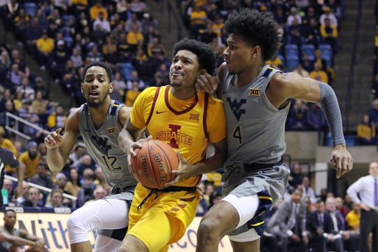 Iowa State guard Prentiss Nixon (11) drives up court as he is defended by West Virginia guards Taz Sherman (12) and Miles McBride (4) during the first half of an NCAA college basketball game Wednesday, Feb. 5, 2020, in Morgantown, W.Va. (AP Photo/Kathleen Batten)